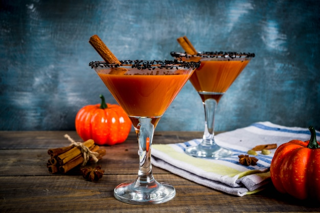 Autumn spicy pumpkin martini with cinnamon, anise stars and black sesame decoration, dark blue background