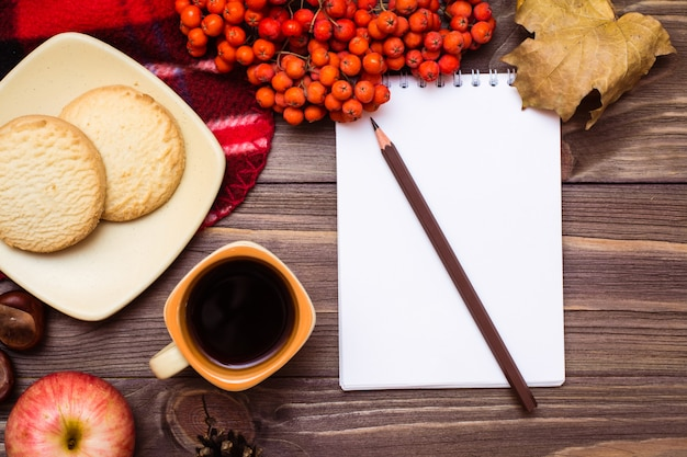 Autumn still life: coffee, cookies, a plaid, a notebook and a pencil on wood
