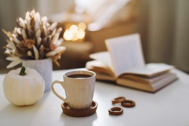 秋の静物。コーヒーカップ、花、本、カボチャ。