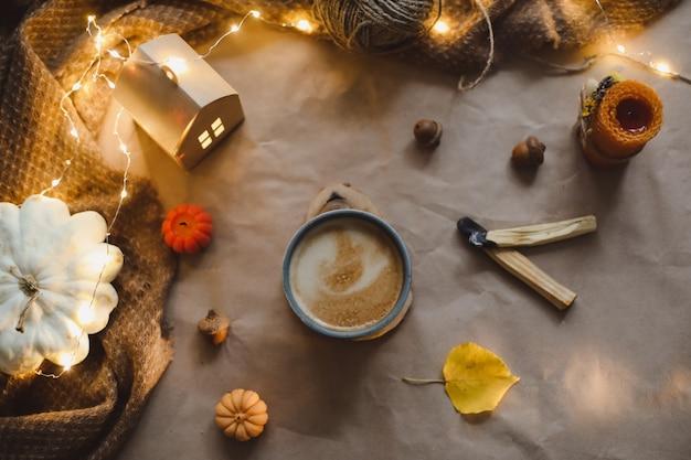 Детали осеннего натюрморта в уютном домашнем интерьере с чашкой, свечами, клетчатой хюгге, хеллоуин и благодарностью ...