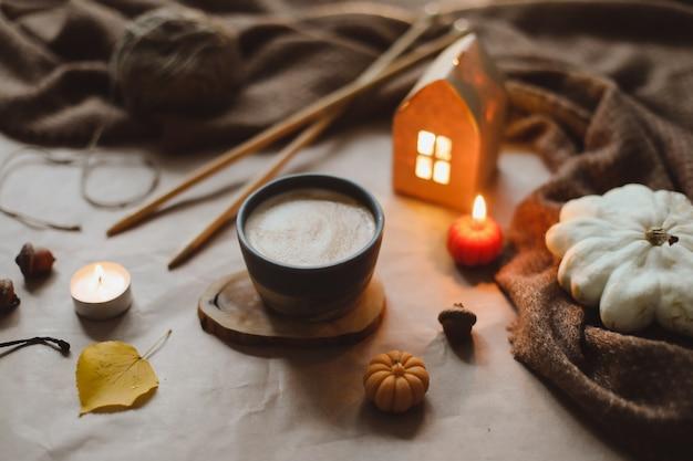 Детали осеннего натюрморта в уютном домашнем интерьере с чашкой, свечами, пледом. домашний декор hygge. хэллоуин и концепция благодарения. осенний баннер