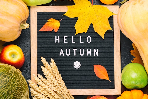Autumn still life image with melon, apples, pears, rye, pumpkins, colorful foliage and letter board with words hello autumn