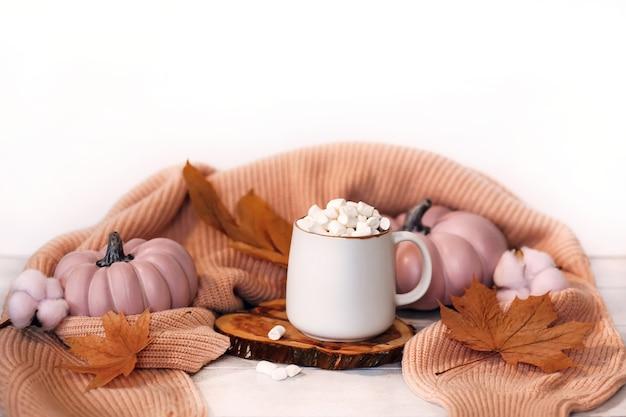ココアマグカップとマシュマロ、ピンクのカボチャ、紅葉、ニットセーターと明るい木製の背景の秋の静物。