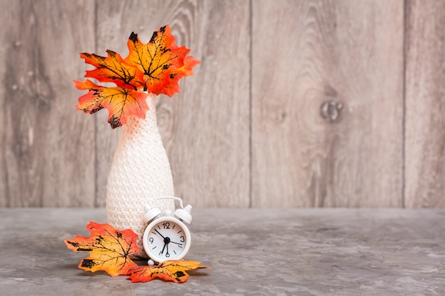Autumn still life. a vase with orange maple leaves and a white alarm clock stand on the table. white-orange-beige color scheme. copy space