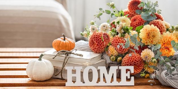 Осенний натюрморт с букетом цветов хризантемы, декоративным словом «дом» и тыквами на размытом фоне.