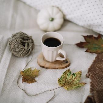 Осенний натюрморт с кофейной чашкой, цветами и тыквами на уютном пледе