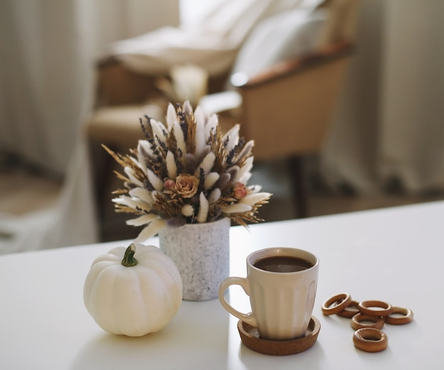 Осенний натюрморт с кофейной чашкой, цветочной книгой и тыквой hygge lifestyle уютное осеннее настроение