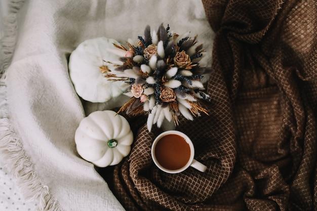 Осенний натюрморт с кофейной чашкой с цветами и тыквами на уютном пледе в стильной осенней постели ... Premium Фотографии