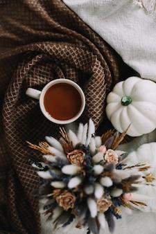 Осенний натюрморт с кофейной чашкой с цветами и тыквами на уютном пледе в стильной осенней постели ...