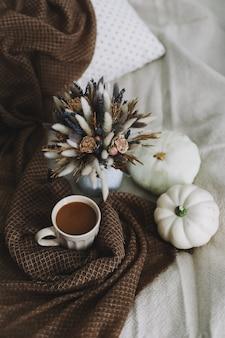 Осенний натюрморт с чашкой кофе с цветами и тыквами на уютном пледе