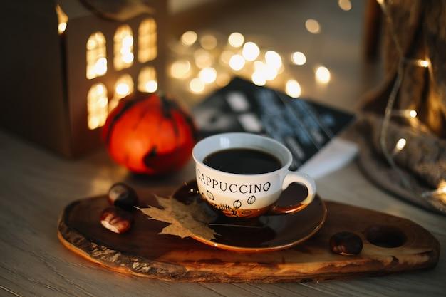 Осенний натюрморт с чашкой капучино на фоне огней гирлянды