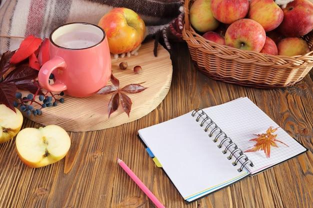 ココア、ノートブック、リンゴのカップで秋の静物。