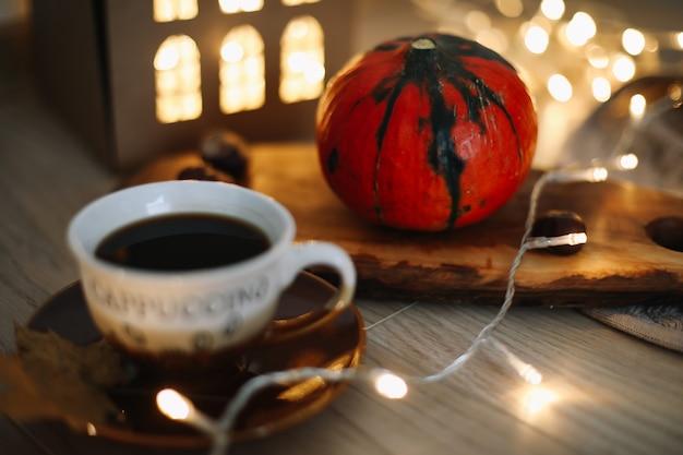 Осенний натюрморт с чашкой кофе, тыквой и листьями на уютном фоне