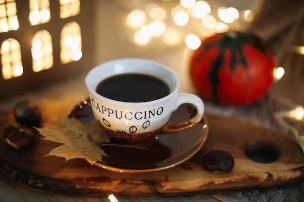 一杯のコーヒーカボチャと居心地の良い背景の葉と秋の静物