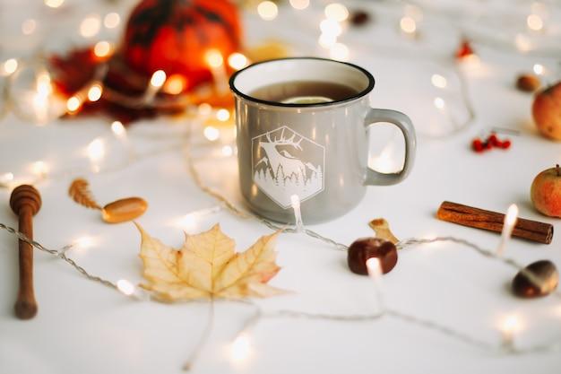 Осенний натюрморт с чашкой чая с лимоном в обрамлении осенних листьев и гирлянды огней