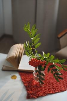 Осенний натюрморт с веткой рябины в вазе и книгой и яблоками в уютном домашнем интерьере