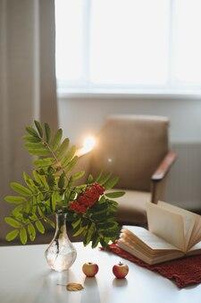 Осенний натюрморт с веткой рябины в вазе и яблоками в уютном домашнем интерьере