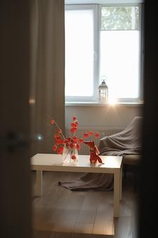 居心地の良い家のインテリアの花瓶に赤いサイサリスのおもちゃのキツネの花の小枝と秋の静物
