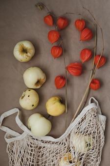 リンゴとホオズキのオレンジ色の花のある秋の静物