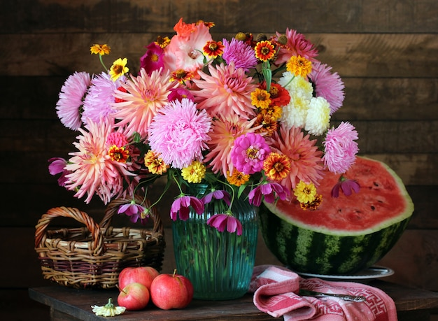 Autumn still life with a bouquet of asters and dahlias in a vase