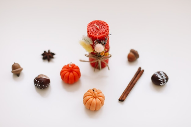 キャンドルカボチャシナモン栗ドングリと白い背景の上の秋の静物上面図 Premium写真