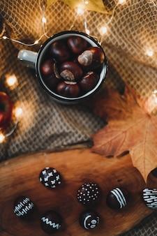 Осенний натюрморт с каштанами в уютной чашке теплое изображение в стиле хюгге