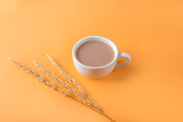 Autumn still life with cup of coffee and beige pampas grass reeds on orange background. minimal, stylish, creative fall still life. flat lay, copy space.