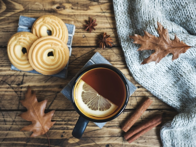 Autumn still life with cup of tea, cookies, sweater and leaves on wooden table.