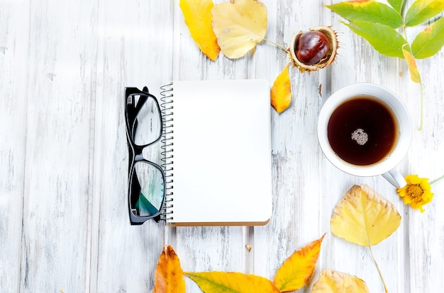 Autumn still life with cup of tea with cookies, empty notebook, eyeglass and leaves on white wooden background