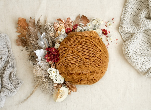 Autumn still life with flowers and knitted elements on a white space close up.
