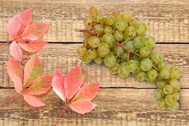 Осенний натюрморт с виноградом и красными листьями на деревянных досках. вид сверху.