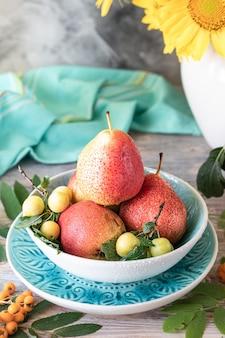 木製の背景に梨とひまわりの花と秋の静物