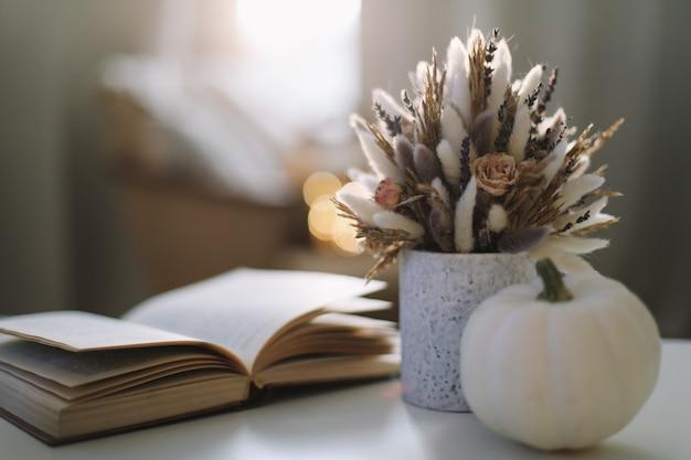 Осенний натюрморт с тыквой и цветами в уютной солнечной гостиной