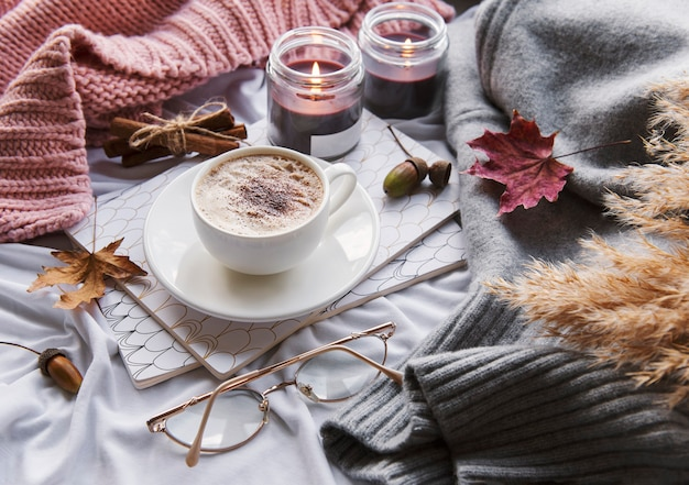 Осенний натюрморт с тыквами, кофе и зажженными свечами. уютная осенняя композиция