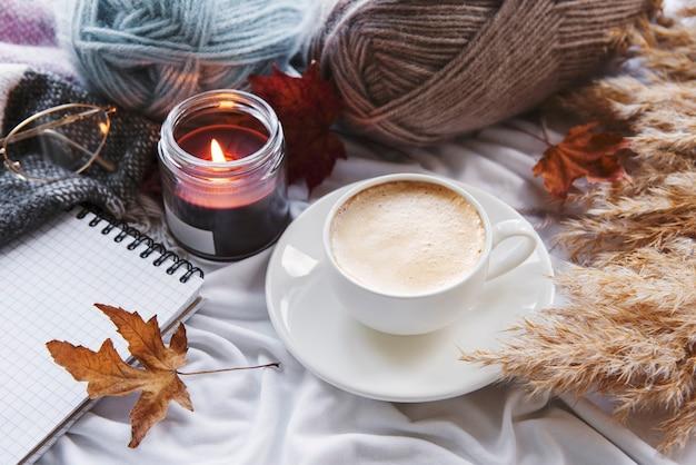 호박, 커피, 불타는 초가 있는 가을 정물. 아늑한 가을 구성