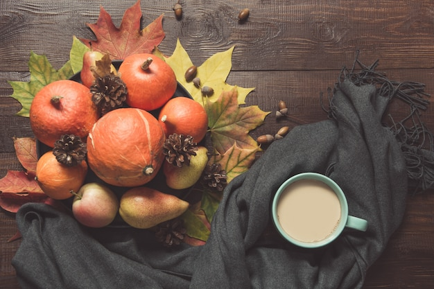 Autumn still life with pumpkins, cup of coffee on board.