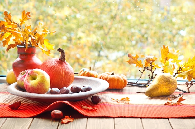 Autumn still life with pumpkins, fruits, chestnuts and dry leaves on a window board on a rainy day