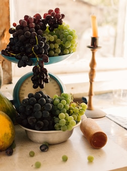 Autumn still life with pumpkins and grapes in a metal bowl, grapes are scattered around on a wooden white table. in the background is a candle in a candlestick. autumn harvest concept.