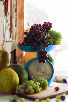 Autumn still life with pumpkins, melons, watermelon, grapes on a scale and in a metal bowl on a wooden white table. autumn harvest concept.