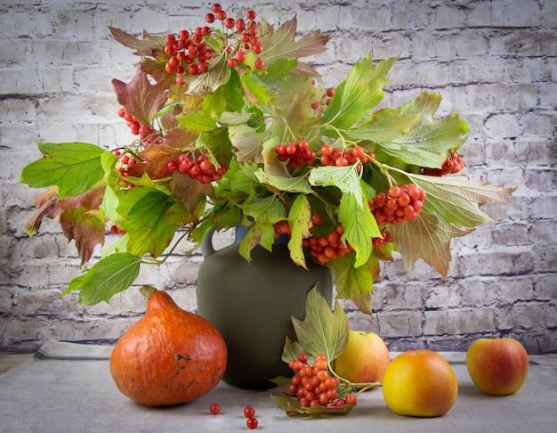 Осенний натюрморт с красной рябиной, яблоками и тыквой.