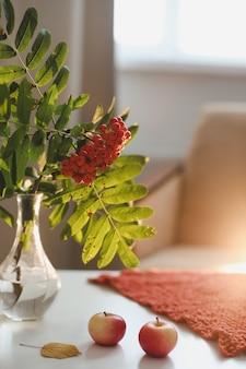 Осенний натюрморт с рябиной и яблоками на белом столе в уютном домашнем интерьере