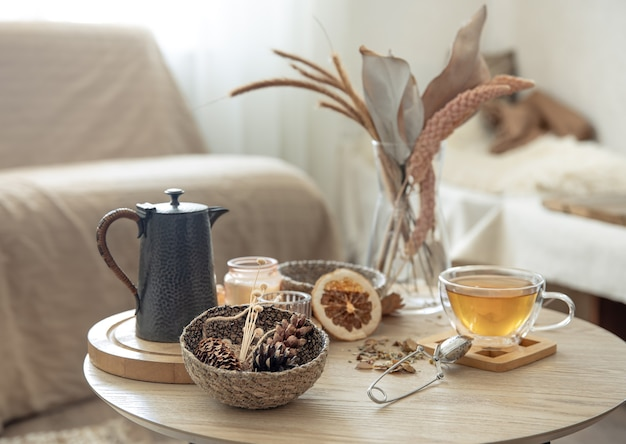 Autumn still life with tea on the table in the interior of the room, copy space.