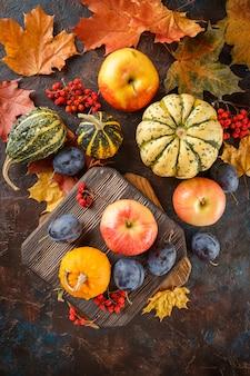 野菜や果物のある秋の静物。カボチャ、リンゴ、プラム、黄色の葉。上面図