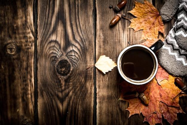 秋のスタイル木製のテーブルにミトンとホットコーヒーのカップ