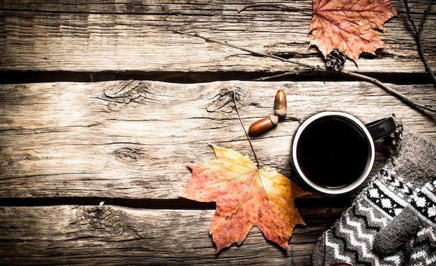 秋のスタイル。ミトンとホットコーヒーのカップ。木製のテーブルの上。
