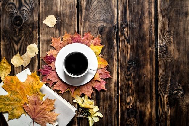 木製の背景に古い本と秋のスタイルのコーヒー