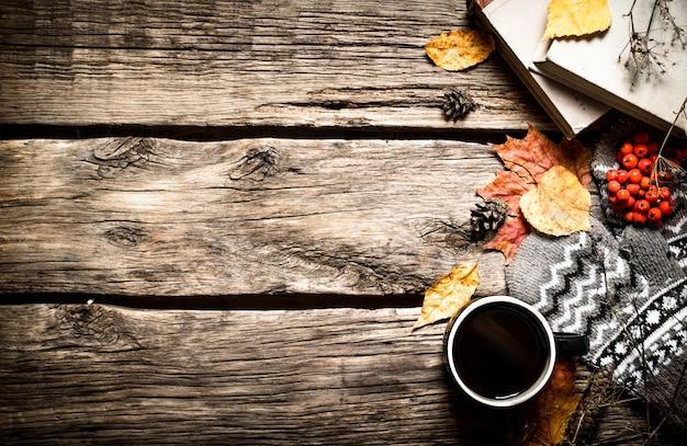 秋のスタイル。古い本とコーヒー。木製の背景に。