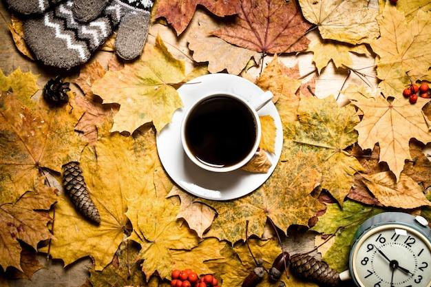 秋のスタイル。紅葉の目覚まし時計とコーヒーのカップ。