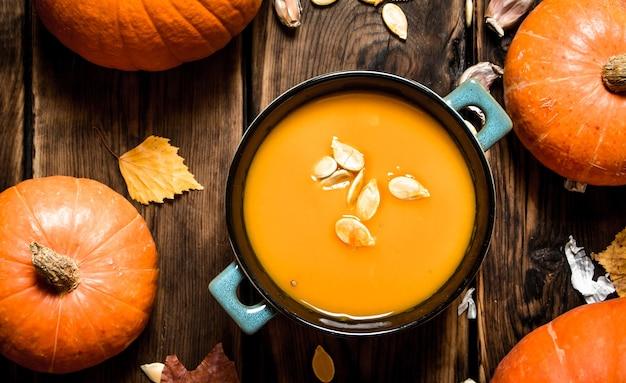 Осенний стиль. суп из свежей тыквы. на деревянном фоне