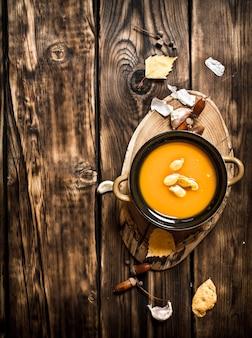 秋のスタイル。新鮮なカボチャスープ。木製の背景に